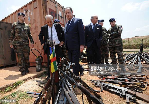 French President Francois Hollande French Defense Minister JeanYves Le Drian and French Foreign Minister Laurent Fabius inspect arms confiscated from...