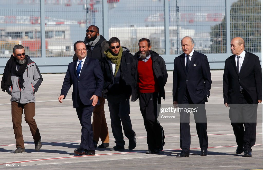 French president Francois Hollande (2nd L), French Foreign Affairs Minister Laurent Fabius and Defence Minister Jean-Yves Le Drian (R) welcome former French hostages (L-R) Marc Feret, Thierry Dol, Pierre Legrand and Daniel Larribe upon their arrival at the military airport of Villacoublay outside Paris, on October 30, 2013 in Velizy-Villacoublay, France. The four French hostages, who were kidnapped by Al-Qaeda 3 years ago in the Islamic Maghreb in northern Niger where they worked, have returned to France following their release on October 29, 2013.