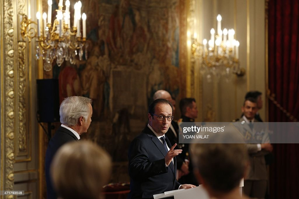 French President Francois Hollande (C) gestures as he delivers a speech, as French Minister of Labour <a gi-track='captionPersonalityLinkClicked' href=/galleries/search?phrase=Francois+Rebsamen&family=editorial&specificpeople=590201 ng-click='$event.stopPropagation()'>Francois Rebsamen</a> (L) looks on, during a Long-Service Award (Medaille du Travail) ceremony at the Elysee Palace in Paris on May 1, 2015. AFP PHOTO / POOL / YOAN VALAT