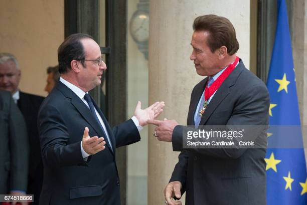 French President Francois Hollande gestures as he speaks with US actor and former governor of California Arnold Schwarzenegger after he was awarded...