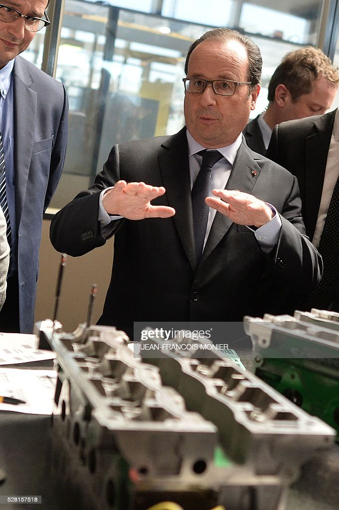French President Francois Hollande gestures in front of a Renault engine cylinder head during a visit at the MK Automotive Mecachrome plant on May 4, 2016 in Sable-sur-Sarthe, northwestern France. / AFP / JEAN