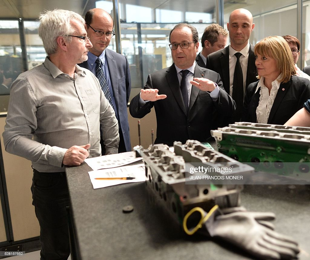 French President Francois Hollande (C) gestures in front of a Renault engine cylinder head during a visit at the MK Automotive Mecachrome plant on May 4, 2016 in Sable-sur-Sarthe, northwestern France. / AFP / JEAN