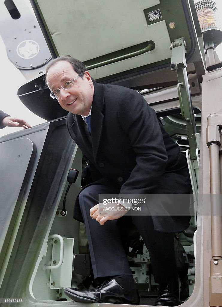 French President Francois Hollande, gets out an armored vehicule of the 12th cuirassiers regiment at the military base of Olivet, central France, as part of a visit to present his New Year's wishes to the French armed forces, on January 9, 2013. AFP PHOTO POOL/JACQUES BRINON