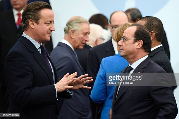 French president Francois Hollande greets British Prime Minister David Cameron as he arrives for the family photo during the COP21 United Nations...