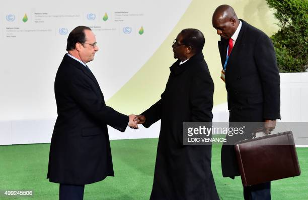 French President Francois Hollande greets Zimbabwean President Robert Mugabe as he arrives for the opening of the UN conference on climate change on...