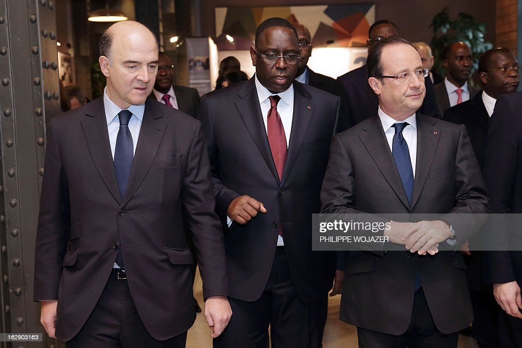 French President Francois Hollande (R), his Senegalese counterpart Macky Sall and Finance Minister Pierre Moscovici (L) arrive at the International Solidarity and Development meeting in Paris, on March 1, 2013. AFP PHOTO POOL/Philippe Wojazer