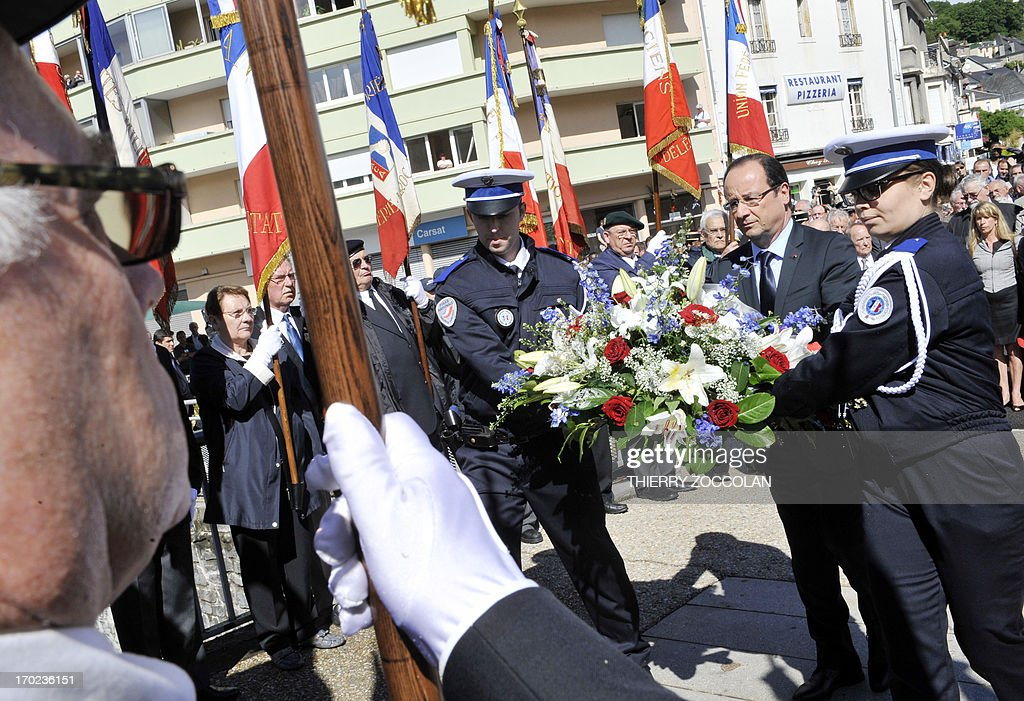 French President Francois Hollande (2nd R) holds a bunch of flowers during a ceremony in Tulle, central France, on June 9, 2013, to commemorate the Nazi massacre of Tulle in 1944.