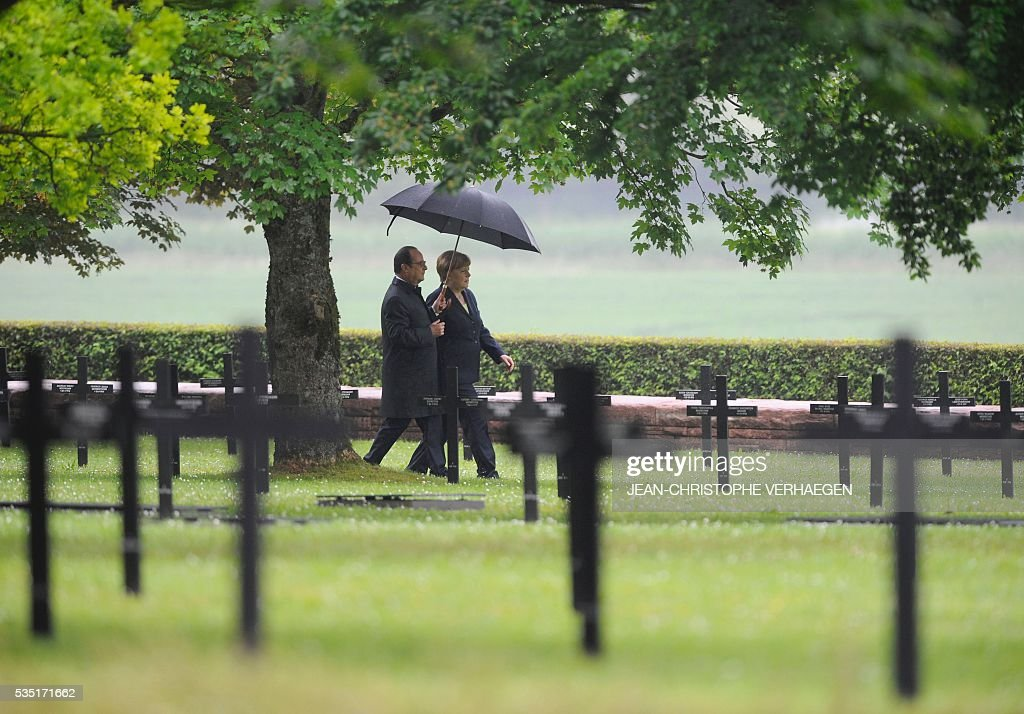 French President Francois Hollande (L) holds an umbrella as he walks beside German Chancellor Angela Merkel at a German cemetery in Consenvoye, northeastern France on May 29, 2016, during a remembrance ceremony to mark the centenary of the battle of Verdun. The battle of Verdun, in 1916, was one of the bloodiest episodes of World War I. The offensive which lasted 300 days claimed more than 300,000 lives. VERHAEGEN
