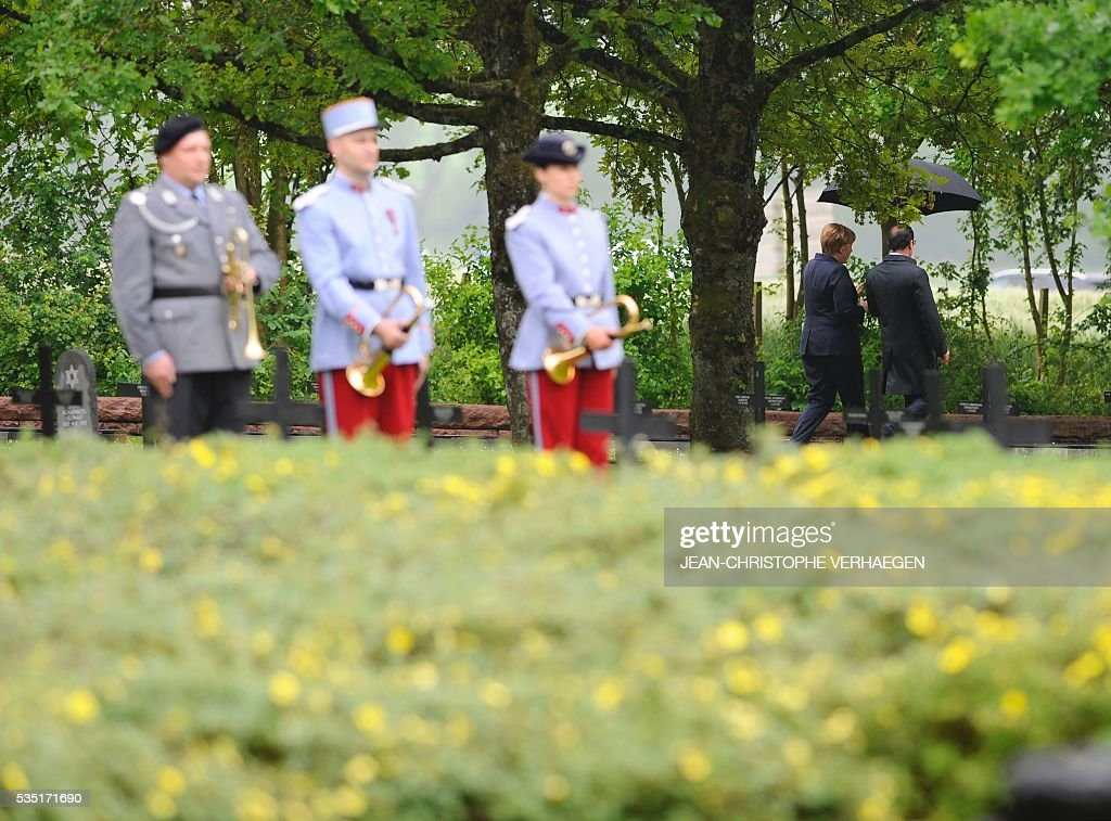 French President Francois Hollande (R) holds an umbrella as he walks beside German Chancellor Angela Merkel at a German cemetery in Consenvoye, northeastern France on May 29, 2016, during a remembrance ceremony to mark the centenary of the battle of Verdun. The battle of Verdun, in 1916, was one of the bloodiest episodes of World War I. The offensive which lasted 300 days claimed more than 300,000 lives. VERHAEGEN