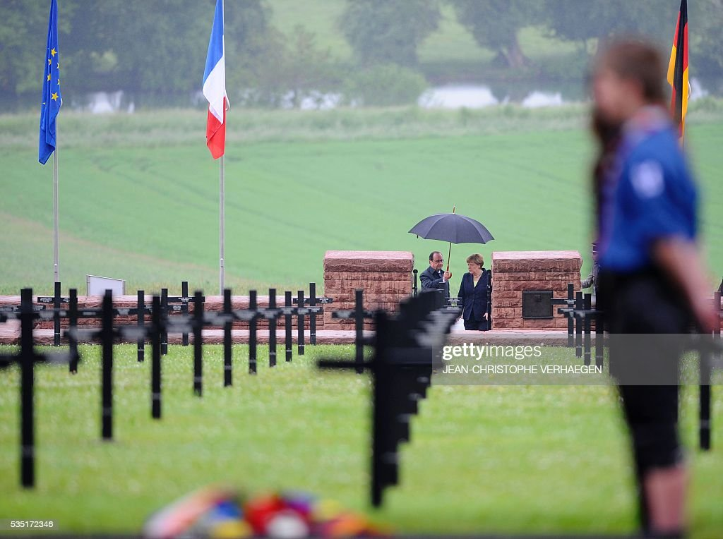 French President Francois Hollande (C-L) holds an umbrella as he walks beside German Chancellor Angela Merkel at a German cemetery in Consenvoye, northeastern France on May 29, 2016, during a remembrance ceremony to mark the centenary of the battle of Verdun. The battle of Verdun, in 1916, was one of the bloodiest episodes of World War I. The offensive which lasted 300 days claimed more than 300,000 lives. VERHAEGEN