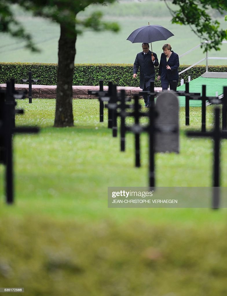 French President Francois Hollande (L) holds an umbrella as he walks beside German Chancellor Angela Merkel as they arrive at a German cemetery in Consenvoye, northeastern France on May 29, 2016, during a remembrance ceremony to mark the centenary of the battle of Verdun. The battle of Verdun, in 1916, was one of the bloodiest episodes of World War I. The offensive which lasted 300 days claimed more than 300,000 lives. VERHAEGEN