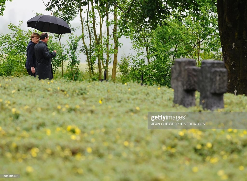 French President Francois Hollande (R) holds an umbrella as he walks beside German Chancellor Angela Merkel at a German cemetery in Consenvoye, northeastern France on May 29, 2016, during a remembrance ceremony to mark the centenary of the battle of Verdun. The battle of Verdun, in 1916, was one of the bloodiest episodes of World War I. The offensive which lasted 300 days claimed more than 300,000 lives. / AFP / POOL / Jean Christophe VERHAEGEN
