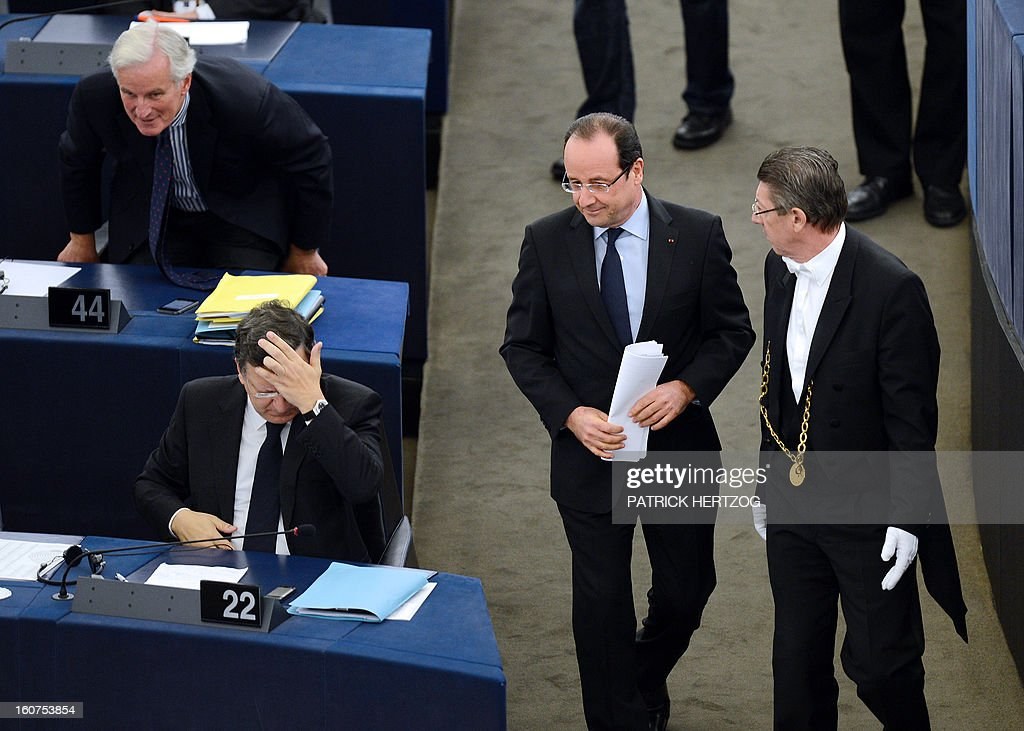 French President Francois Hollande (C) holds documents as he walks past European Commission head Jose Manuel Barroso (L) and EU internal market and services commissioner Michel Barnier (top-left) on February 5, 2013 at the European Parliament, in Strasbourg, eastern France. Hollande delivered a speech in front of the European Parliament, two days before a summit on the EU budget.
