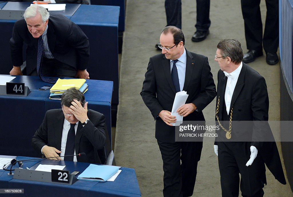 French President Francois Hollande (C) holds documents as he walks past European Commission head Jose Manuel Barroso (L) and EU internal market and services commissioner Michel Barnier (top-left) on February 5, 2013 at the European Parliament, in Strasbourg, eastern France. Hollande delivered a speech in front of the European Parliament, two days before a summit on the EU budget. AFP PHOTO / PATRICK HERTZOG
