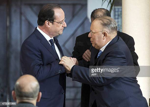 French President Francois Hollande holds hands with Paris Mosque rector Dalil Boubakeur after delivering speeches at the 'Grande Mosquee de Paris'...