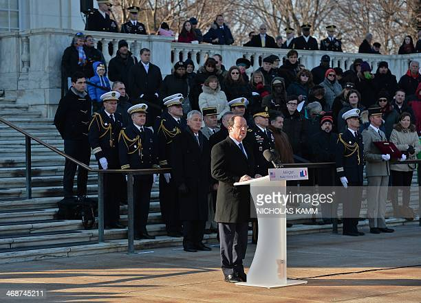 French President Francois Hollande honors the Unknown Soldier of WWII with the Legion of Honor as US Defense Secretary Chuck Hagel looks on after...