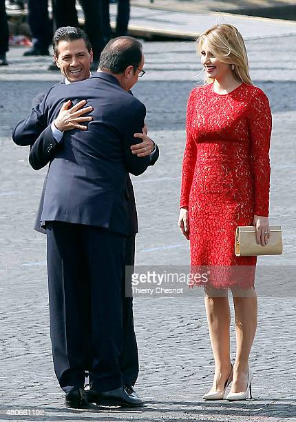 French President Francois Hollande hugs Mexican President Enrique Pena Nieto next to Mexican First Lady Angelica Rivera during the annual Bastille...