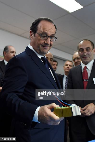 French President Francois Hollande inspects a sonar transducer during a visit to the French electrical systems manufacturing company Thales on...