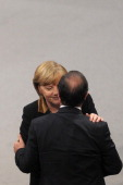 French President Francois Hollande is cheered by German Chancellor Angela Merkel after his speech during the joint session of the French National...