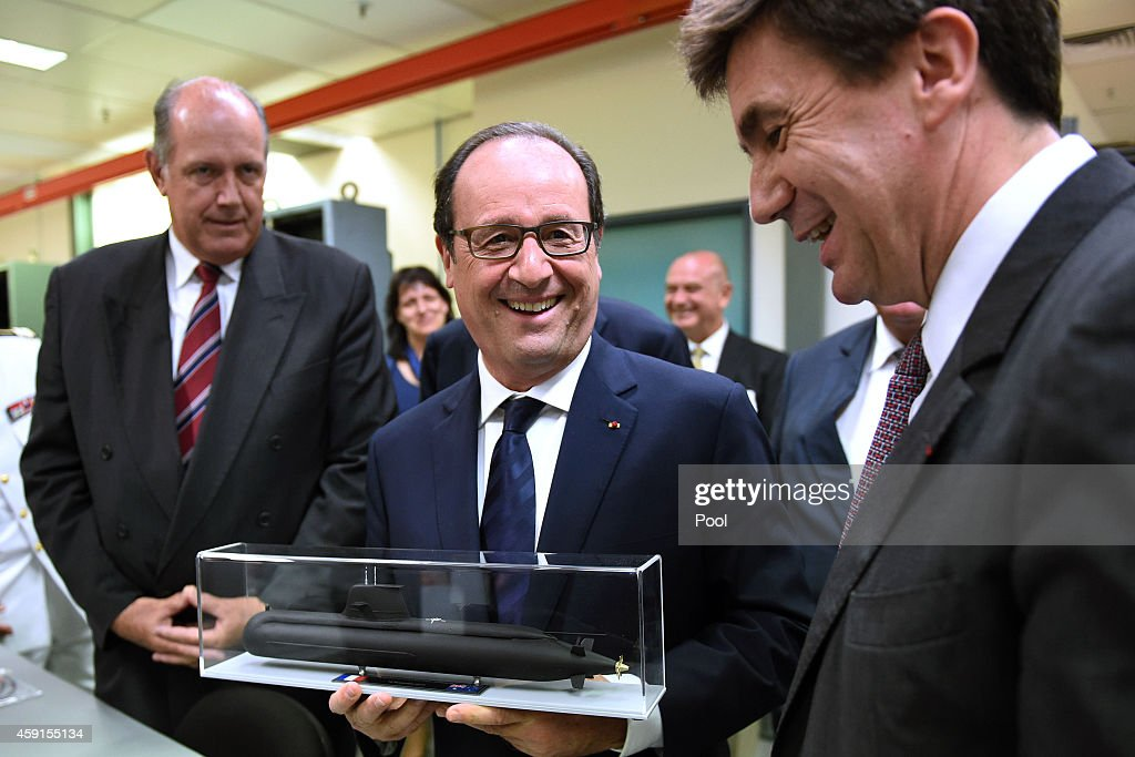 French President Francois Hollande, (centre) is presented a model of the Australian Navy's Collins Class submarine with Australian Minister for Defence, Senator <a gi-track='captionPersonalityLinkClicked' href=/galleries/search?phrase=David+Johnston+-+Politician&family=editorial&specificpeople=7915223 ng-click='$event.stopPropagation()'>David Johnston</a>, (left), and Executive Vice President of Thales Defence Mission Systems, Pierre Eric Pommellet, (right) during a visit to French defence manufacturing company, Thales, on November 18, 2014 in Sydney, Australia. French President Francois Hollande is attending meetings in Sydney and Canberra following the G20 Leaders Summit in Brisbane.