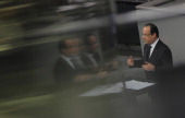 French President Francois Hollande is reflected in a glass panel as he delivers a speech at the German lower house of Parliament Bundestag on January...