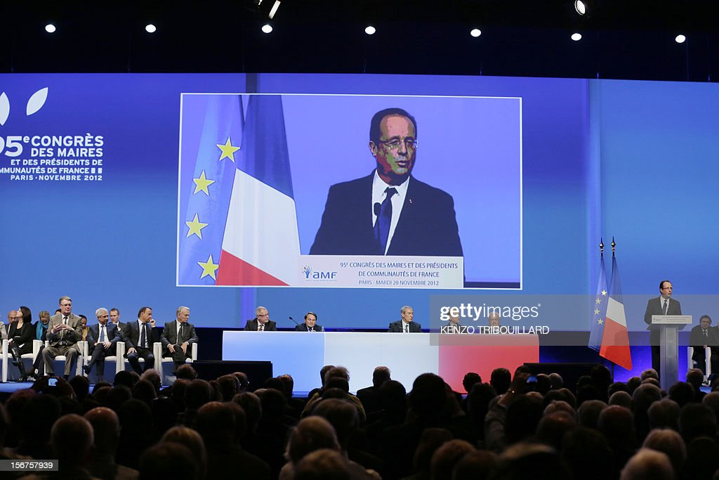 French President Francois Hollande (R) is seen on a giant screen as he delivers a speech during the opening ceremony of the 95th French Mayors congress, on November 20, 2012 in Paris.