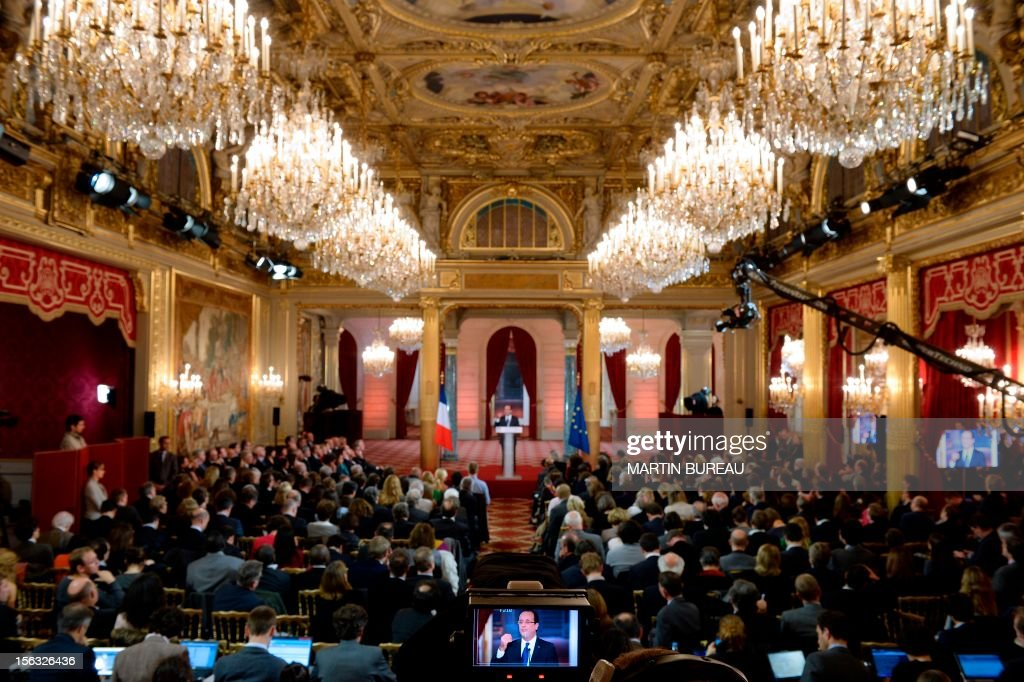 French President Francois Hollande is seen on a TV screen as he gives his first major press conference at the Elysee Place in Paris on November 13, 2012. Hollande holds his first major press conference amid rising discontent over the flagging economy and a slump in his personal poll ratings.