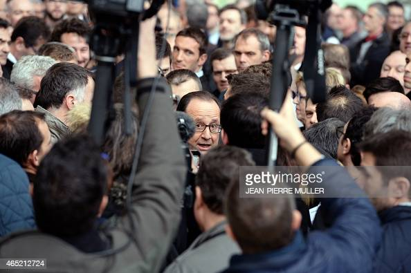 French president Francois Hollande is surrounded by journalists upon his arrival to visit the assembly line of Rafale fighter jets at the factory of...