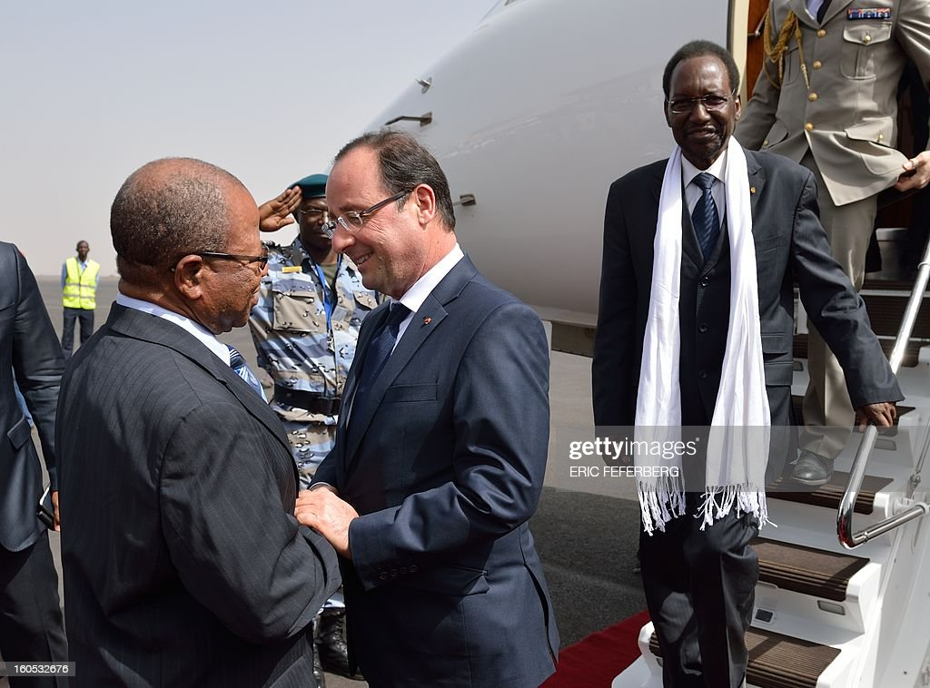 French President Francois Hollande (C) is welcomed by Malian Prime minister Django Sissoko (L) as he arrives at the Bamako airport flanked by Mali's interim president Dioncounda Traore (R) on February 2, 2013. Hollande received a rapturous welcome Today as he visited Mali to push for African troops to take over a French-led offensive that drove back Islamist rebels from the country's desert north. POOL AFP/PHOTO ERIC FEFERBERG