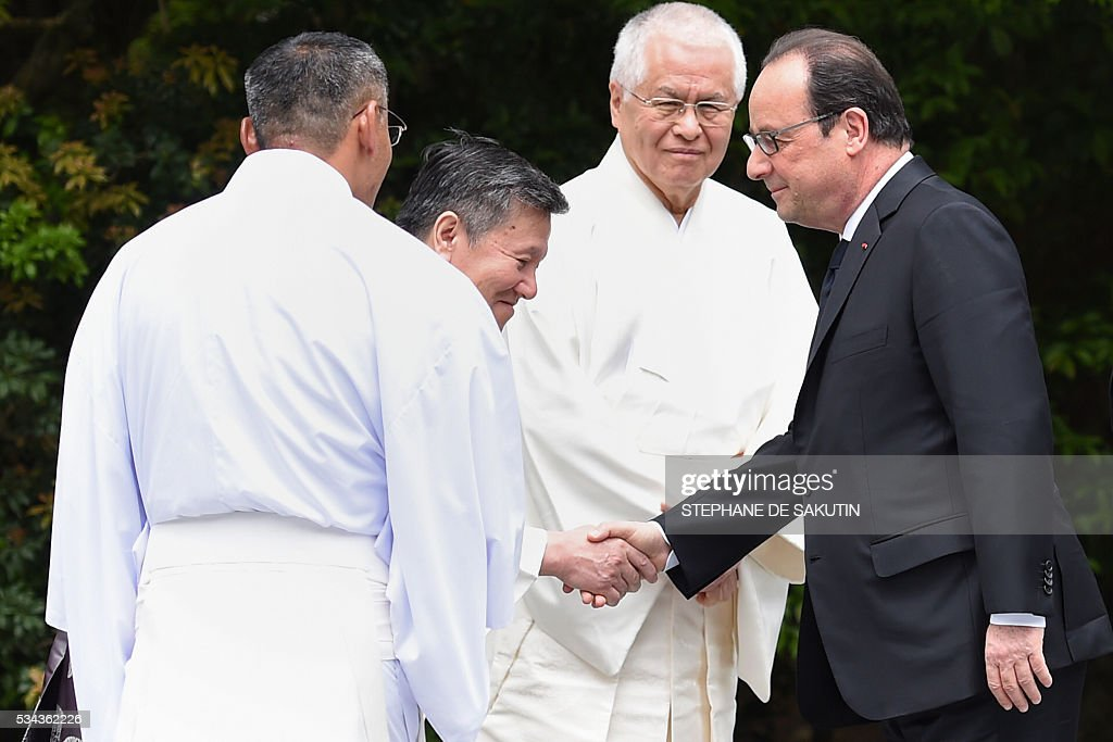 French President Francois Hollande (R) is welcomed by Shinto priests as he arrives at Ise-Jingu Shrine in the city of Ise in Mie prefecture, on May 26, 2016 on the first day of the G7 leaders summit. World leaders kick off two days of G7 talks in Japan on May 26 with the creaky global economy, terrorism, refugees, China's controversial maritime claims, and a possible Brexit headlining their packed agenda. / AFP / STEPHANE