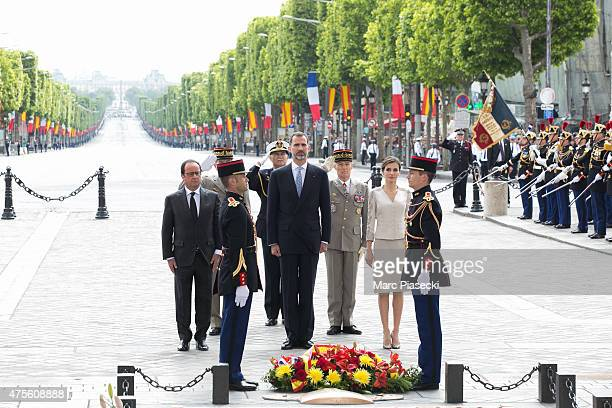 French President Francois Hollande King Felipe of Spain and Queen Letizia of Spain observe a minute of silence after placing a funeral spray at the...