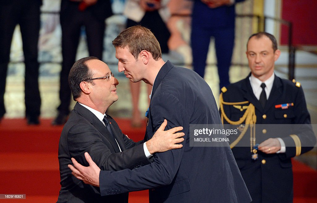 French President Francois Hollande (L) kisses French swimmer Alain Bernard, gold medalist at the 2012 London olympics games, after awarding him with the French Legion d'Honneur during a ceremony on March 1, 2013 in Paris. AFP PHOTO / POOL / MIGUEL MEDINA