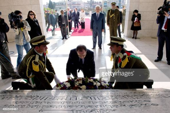 French President Francois Hollande lays a wreath at the grave of late Palestinian leader Yasser Arafat watched by Palestinian authority president...