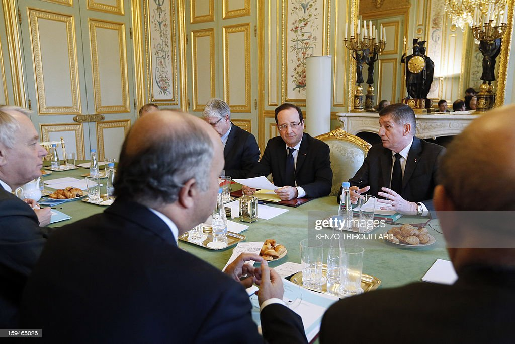 French President Francois Hollande (C) leads a meeting focused on the Malian situation next to his military chief of staff Benoit Pugat (2ndR) and General Secretary of the Elysee presidential palace, Pierre-Rene Lemas (2ndL) and with French Defence minister, French Foreign minister, French Prime Minister Jean-Marc Ayrault (L) and French Interior minister, on January 14, 2013 at the Elysee Presidential palace in Paris. More than 60 Islamists were killed in their bases near the northern Malian city of Gao under intense bombardment by French air power, a security source and residents said today. 'France has attacked Islam. We will strike at the heart of France,' said Abou Dardar, a leader of Movement for Oneness and Jihad in West Africa, an offshoot of Al Qaeda in the Islamic Maghreb (AQIM), speaking to AFP by telephone. AFP PHOTO / POOL / KENZO TRIBOUILLARD