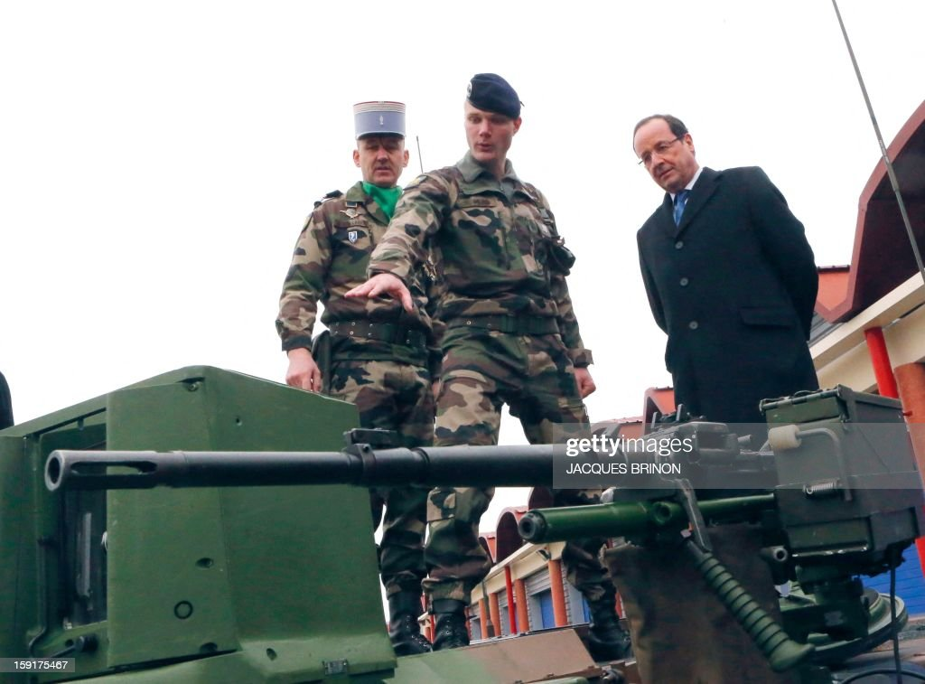 French President Francois Hollande (R) listens to a soldiers of the 12th cuirassiers regiment as he visits the military base of Olivet, central France, as part of a visit to present his New Year's wishes to the French armed forces, on January 9, 2013. AFP PHOTO POOL/JACQUES BRINON