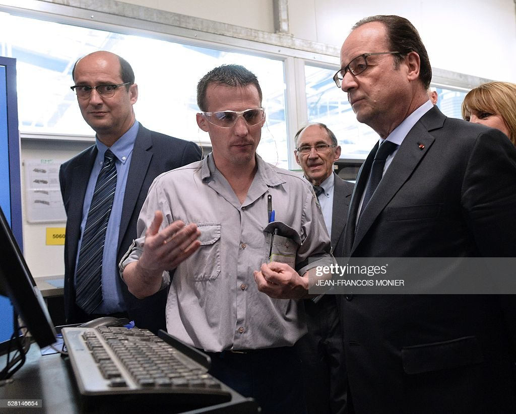 French President Francois Hollande (R) listens to a worker as he visits the MK Automotive Mecachrome plant on May 4, 2016 in Sable-sur-Sarthe, northwestern France. / AFP / JEAN