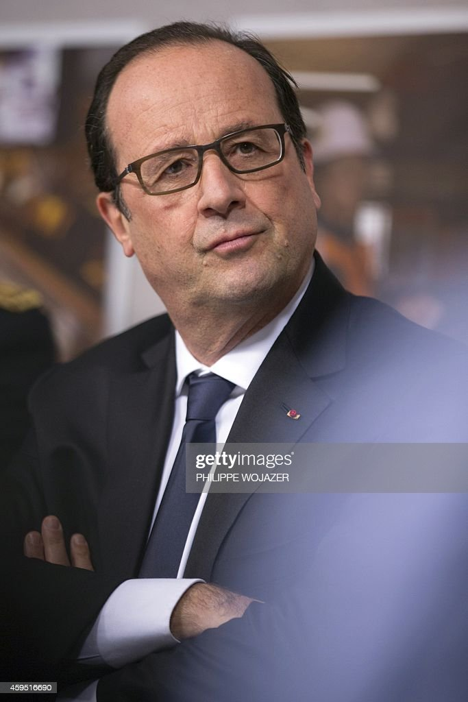 French President Francois Hollande listens to ArcelorMittal workers as he visits their union meeting room during a visit at the ArcelorMittal steel...