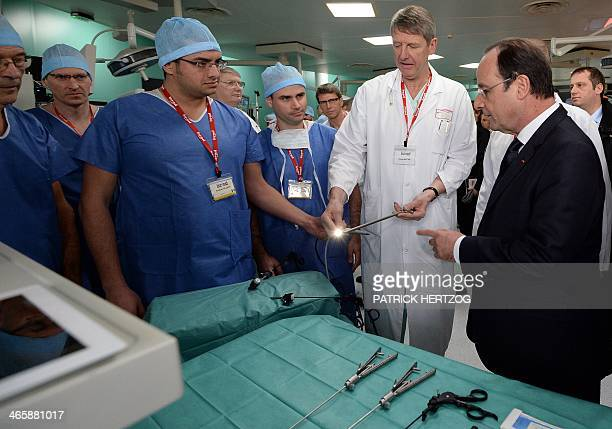 French President Francois Hollande listens to explanations as he looks at robotic technology able to perform 'miniinvasive' cybersurgery during a...