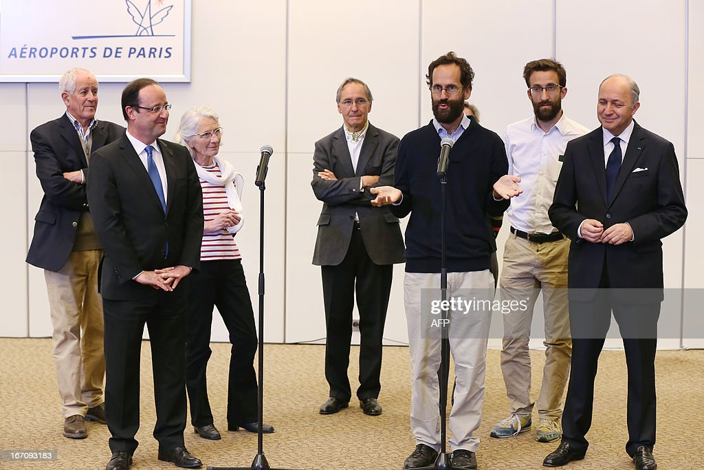 French President Francois Hollande (L) listens to former hostage Tanguy Moulin-Fournier (C) flanked by his brother Cyril Moulin-Fournier (2ndR) arriving from Yaounde, on April 20, 2013 at the Orly airport near Paris. The French members of the Moulin-Fournier family were released after being held in Nigeria for two months by an al-Qaeda-linked Islamist group called Boko Haram and left Cameroon for France on April 19, 2013 accompanied by French Foreign Minister Laurent Fabius (R).