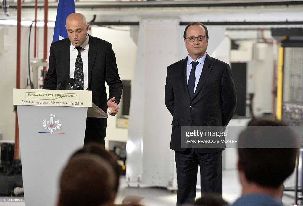 French President Francois Hollande (R) listens to Mecachrome's French Chief Executive Officer Arnaud de Ponnat speaking during a visit at the MK Automotive Mecachrome plant on May 4, 2016 in Sable-sur-Sarthe, northwestern France. / AFP / JEAN