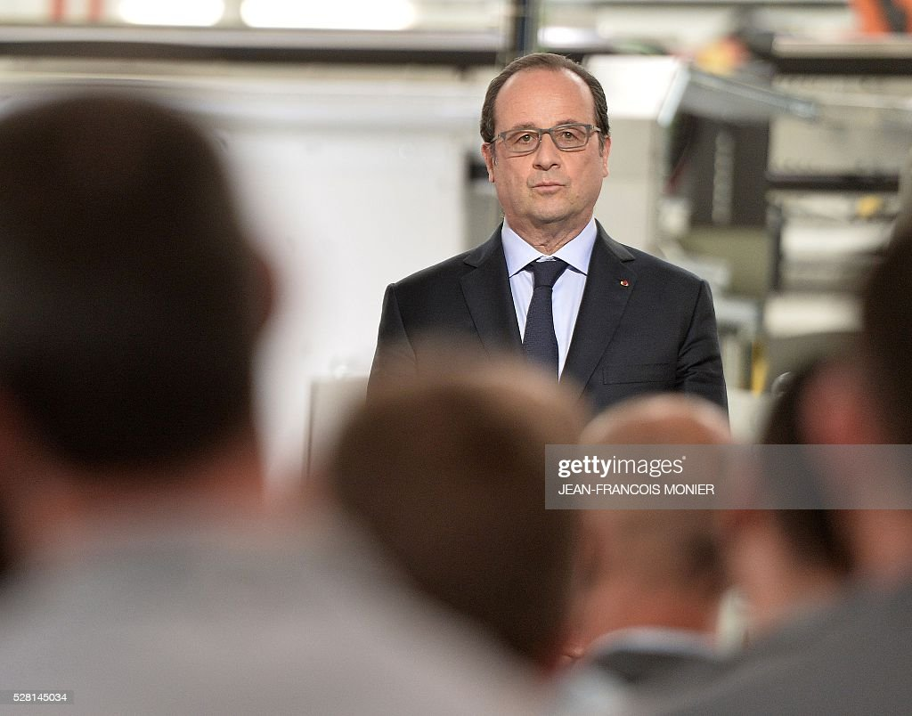 French President Francois Hollande listens to Mecachrome's French Chief Executive Officer speaking during a visit at the MK Automotive Mecachrome plant on May 4, 2016 in Sable-sur-Sarthe, northwestern France. / AFP / JEAN