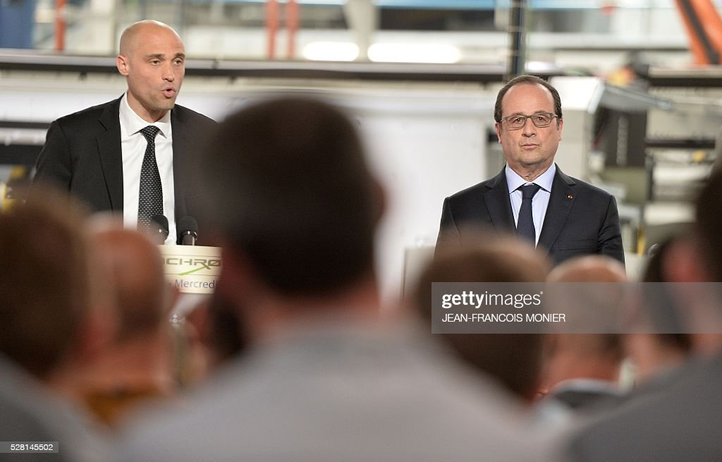 French President Francois Hollande (R) listens to Mecachrome's French Chief Executive Officer Arnaud de Ponnat during a visit at the MK Automotive Mecachrome plant, on May 4, 2016 in Sable-sur-Sarthe, northwestern France. / AFP / JEAN