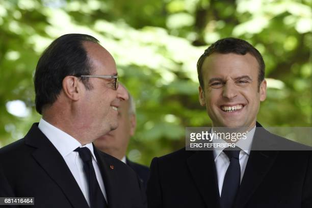 TOPSHOT French President Francois Hollande looks as newly elected president Emmanuel Macron smiles during a ceremony to mark the anniversary of the...