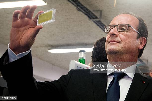 French President Francois Hollande looks at a connected object as he visits the newly inaugurated 'Cite de l'Objet Connecte' in SaintSylvaind'Anjoy...