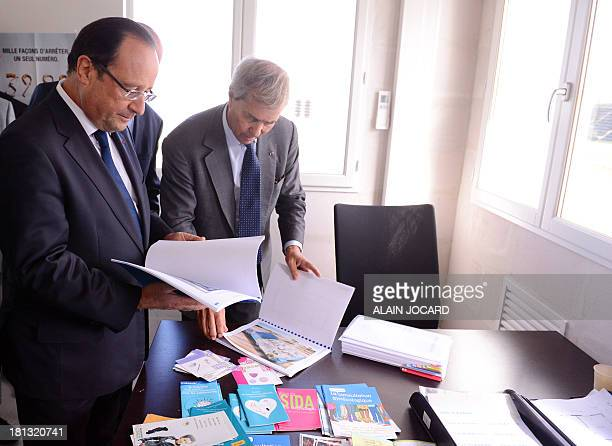 French President Francois Hollande looks at documents related to the 'BlueHouse' electric powered building project alongside French businessman...