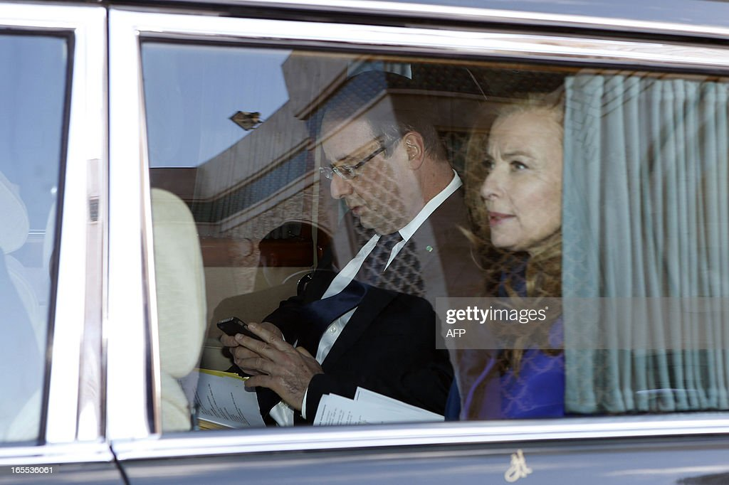 French President Francois Hollande (C) looks at his mobile phone as he sits next to his partner Valerie Trierweiler in a limousine after visiting the Hassan II mosque in Casablanca on April 4, 2013. French President Hollande is on his second-day state visit to Morocco.