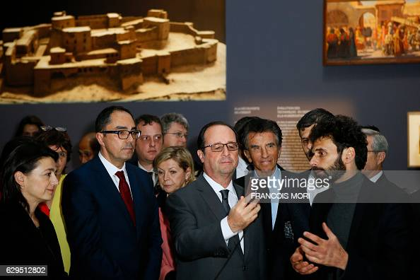 French President Francois Hollande looks on a digital tablet as Louvre Museum President Jean Luc Martinez and French researcher Yves Ubelmann look on...