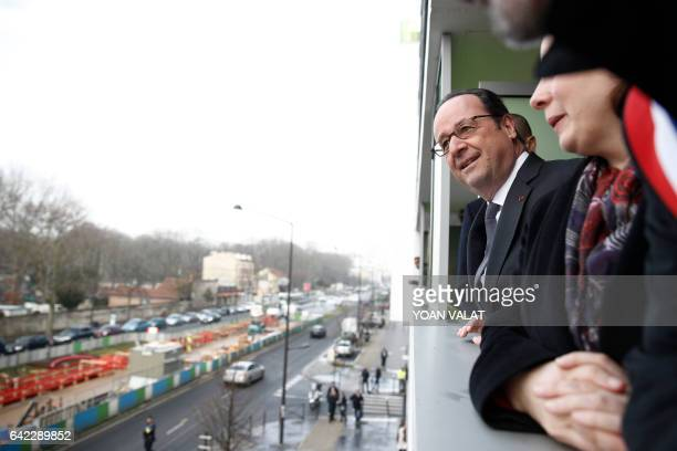 French President Francois Hollande looks out from the balcony of an apartment in Ivry Sur Seine south of Paris on February 17 during a visit on...