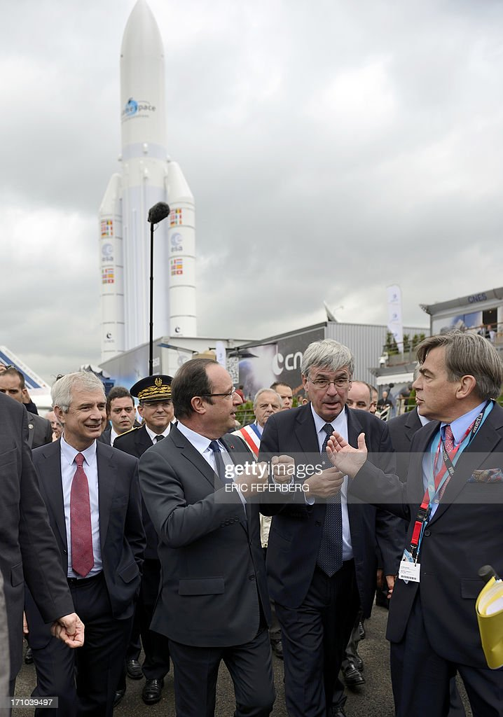 French President Francois Hollande (2nd L) next to Parliament President Claude Bartolone (L) speaks with Chairman and CEO of International Paris Air Show Emeric d'Arcimoles (R) in front of an Ariane 5 rocket at Le Bourget airport, near Paris on June 21, 2013, during the 50th International Paris Air show.AFP PHOTO / ERIC FEFERBERG
