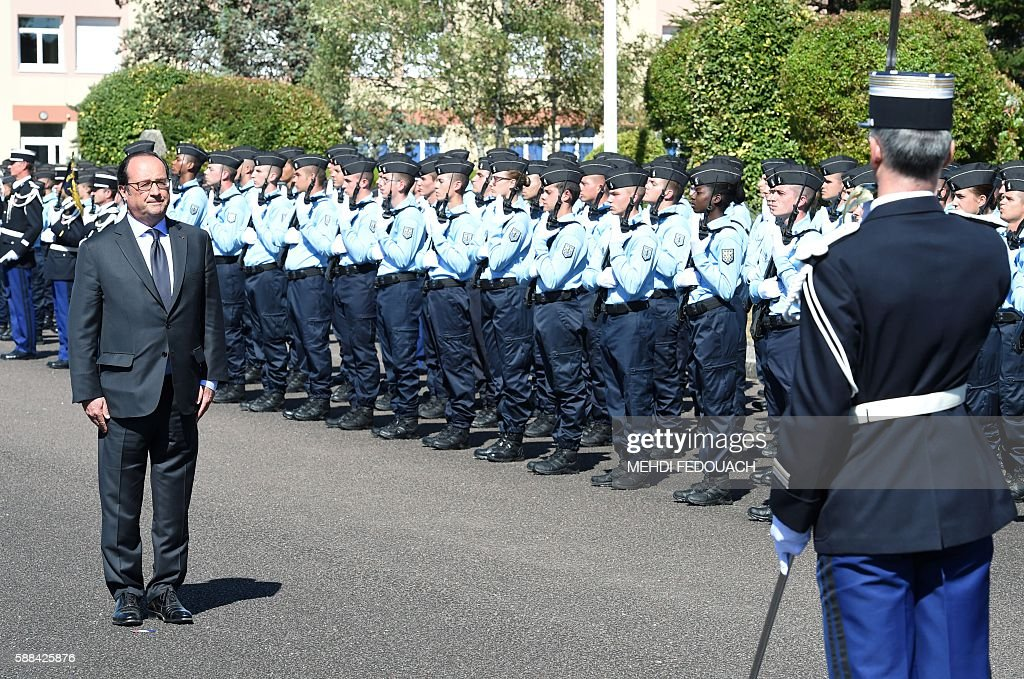French President Francois Hollande observes a military honour guard of French young operational reservists during a visit at the French Gendarmerie...